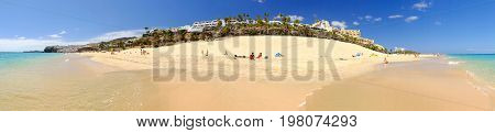 MORRO JABLE FUERTEVENTURA SPAIN - JUNE 14 2017: View on the beach Playa de Matorral with unknown tourists on the Canary Island Fuerteventura Spain. Panorama format.