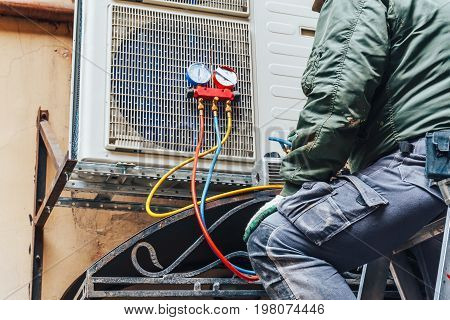Worker repairs air conditioner on the wall, Air Conditioning Repair concept