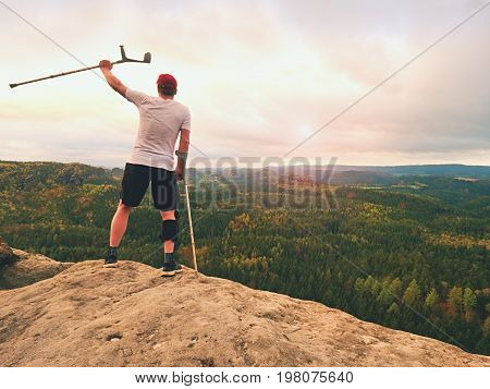 Man Tourist After Accident Use Knee Brace Features  And Forearm Crutches. Man Looking Over