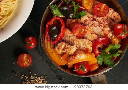 Fried chicken with vegetables on the pan and Italian pasta with a parmesan cheese basil olives paprica and tomatoes on a plate. Healthy food copncept. Top view copy space.