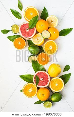 Fresh citrus fruit assortment on white table. Different citrus fruit. Fruit food background. Healthy eating and diet.
