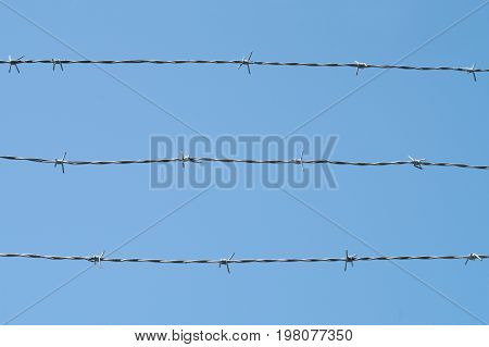 iron metal fence barbed wire boundary security protection prohibited zone on blue sky