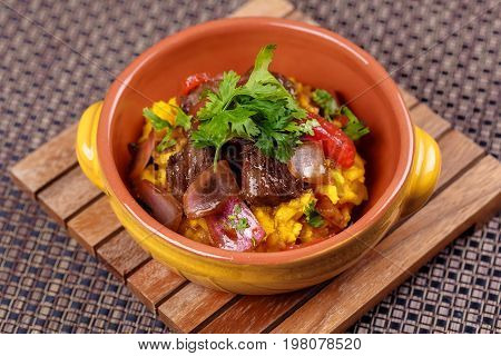 Grilled meat with raditional spanish rice decorated parsley in bowl on wooden board