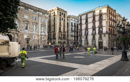 BARCELONA, SPAIN - MAY 2017: Cleaners brigade are starting to sweep square of Barcelona town