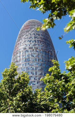 BARCELONA, SPAIN - May 2017: View from green trees on Torre Agbar in Barcelona, Spain. 38 stores skyscraper, built in 2005 by Jean Nouvel.