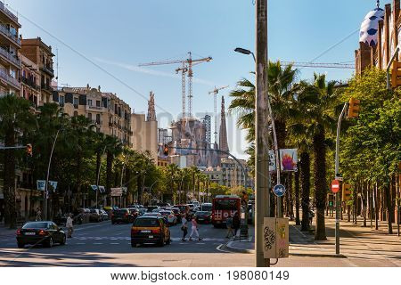 BARCELONA, SPAIN - MAY 2017: Street traffic at Barcelona town with Sagrada Familia on a background, Spain