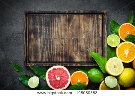 Fresh citrus fruit assortment. Whole and sliced citrus fruit on black slate table. Fruit food background. Top view copy space.