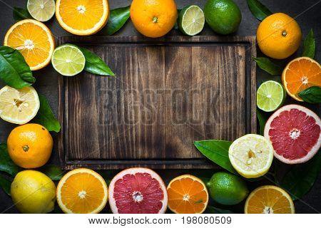 Fresh citrus fruit assortment. Different citrus fruit around cutting board. Fruit food background.