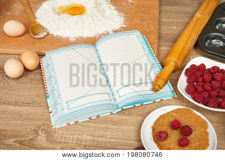 Blank cooking book and ingredients for baking cookies - flour, broken egg, cherry, strawberry on wooden background. Raw food and kitchen utensils. Healthy food concept.