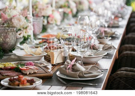 Decorated table, a plate of neatly arranged napkin, fork and knife. Beautifully decorated table with white plates, crystal glasses, linen napkin.