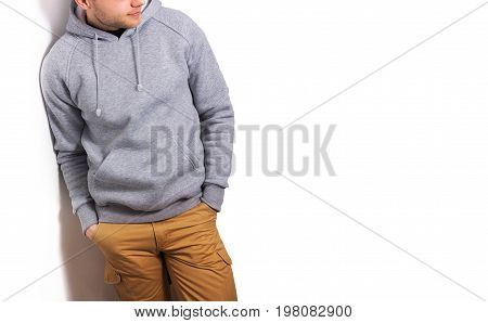 the guy in the blank grey hoodie sweatshirt stand smiling on a white background mock up free space logo template for print design