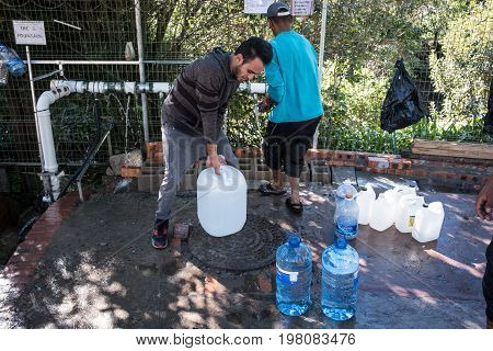 Cape Town South Africa - circa July 2017. As the devestating drought continues in Cape Town people fill up water bottles and containers at the many mountain springs running