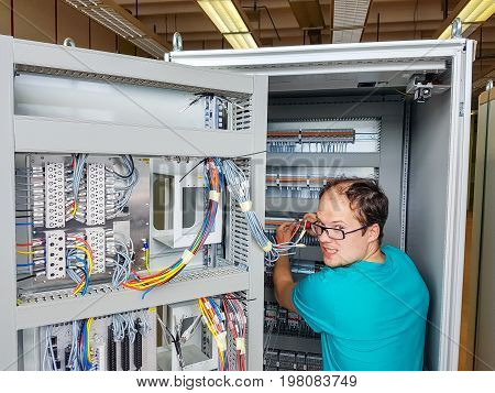 Electrical engineer configuring wires. Electrician repairing substation cubicle.