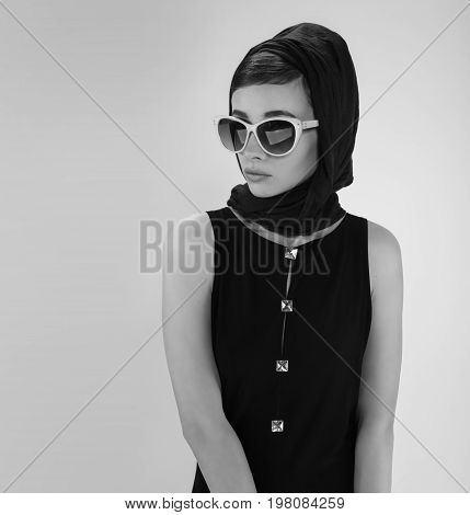 beautiful young woman in retro style with sunglasses and a head scarf black and white photography