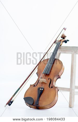 An Old Violin leaned by a stool on a white background