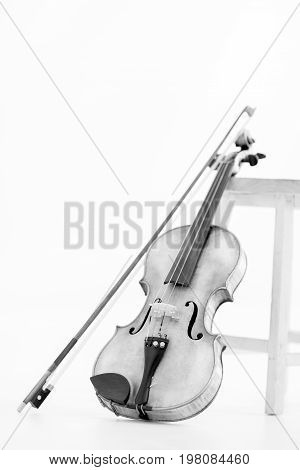 Black and white photo of an Old Violin leaned by a stool