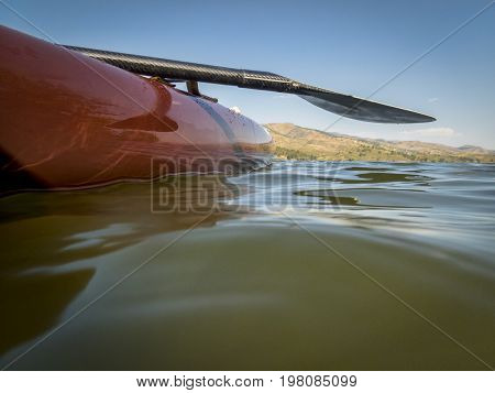Stand up paddleboard with a paddle on a lake, partially underwater shot