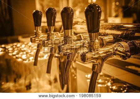 Chromed taps for draft beer in a modern bar. Detail of beer machine beer dispenser close-up selective focus retro style toning