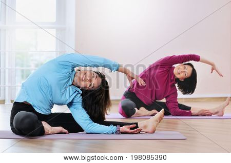 Active Sportive Mature Women Doing Exercise In Fitness Studio