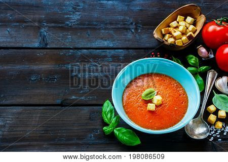Freshly made Gazpacho Tomato summer cream soup in bowl and basil on wooden background. Selective focus copy space.