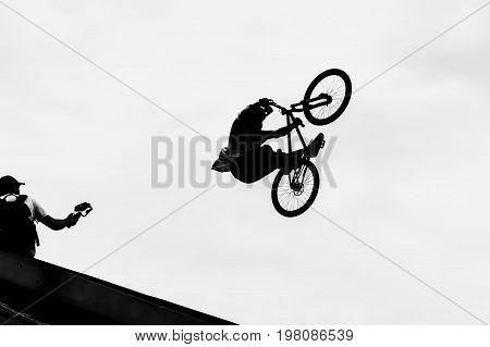 BMX bike jumping in sky on high speed, black and white silhouette. Extrem Sport