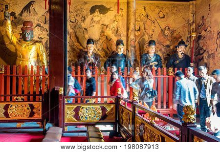 Shanghai, China - Nov 6, 2016: Inside the 600-year-old Old City God Temple. Visitors enter the main hall to pay respect. Statues of gigantic Taoist guards stand along the back wall. Low-light image.