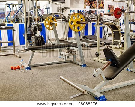 Fitness Room with jogging treadmill and exercise machine. Group of treadmill in row big sport gym. Empty gym with sportsmen and sportswomen pictures on walls. Releases - to portraits on wall.