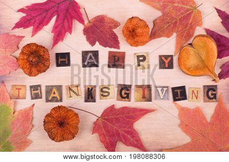 Happy Thanksgiving text with autumn leaves and objects on vintage surface