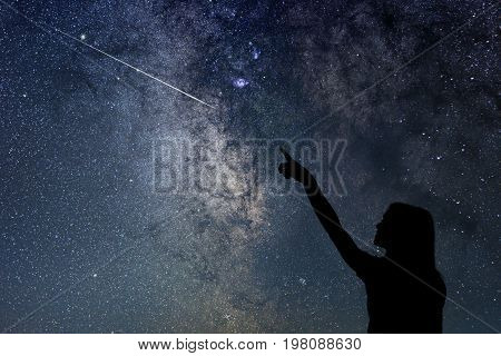 Girl looking at the stars. Girl pointing a shooting star.