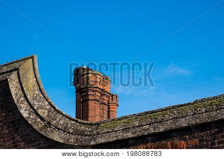 Detail Of Rooftop Red Brick Chimneys In Tudor Architecture Building