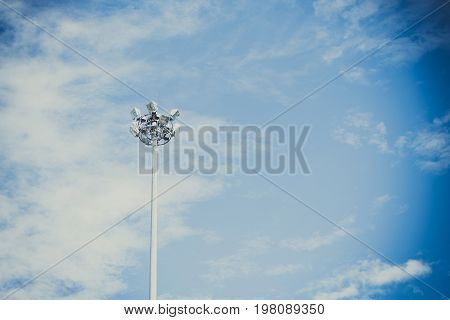 Lamp post electricity industry with blue sky background. Spotlight tower vintage tone.