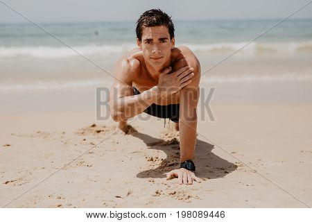 Young Man Doing Push-ups On The Ocean Beach.