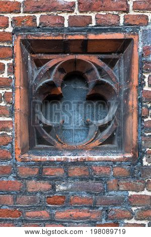 Detail Of Tudor Architecture Exterior Rose-shaped Wall Window Slit