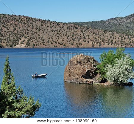 A fisherman in a small aluminum boat trolls for fish past a little boulder island with trees in Prineville Reservoir in Central Oregon on a sunny summer morning.