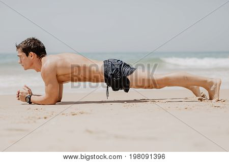 Fitness Man Doing Push-up Exercise On Beach. Portrait Of Fit Guy Working Out His Arm Muscles And Bod