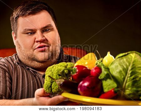 Diet fat man eating healthy food with vegetables for overweight male. Male trying to lose weight first time .Hungry person ready to eat everything. He is trying to go on a diet.