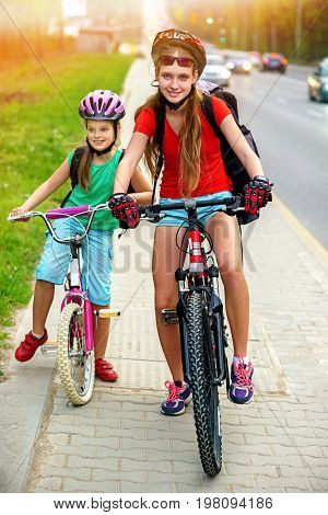 Bikes bicyclist girl. Girls wearing bicycle helmet and glass with rucksack ciclyng bicycle. Girls children cycling on yellow bike lane. Color tone on shiny sunlight background. There are cars on the