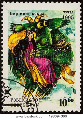 Moscow Russia - August 02 2017: A stamp printed in Uzbekistan shows woman and monster bird a scene from Asian fairy tale
