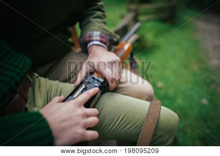 man holds in his hand an old shotgun.Black background