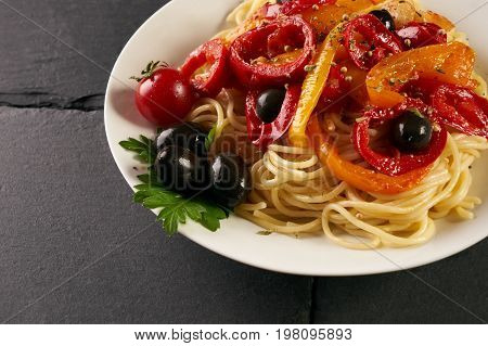 Italian pasta with olives cherry tomatoes paprika bell pepper and cheese in a white plate on dark slate background with copy space. Healthy and vegetarian food . closeup copy space