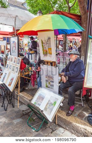 PARIS, FRANCE - JUNE 6, 2012: A Parisian artist at his outdoor stall in Montmartre in Paris.