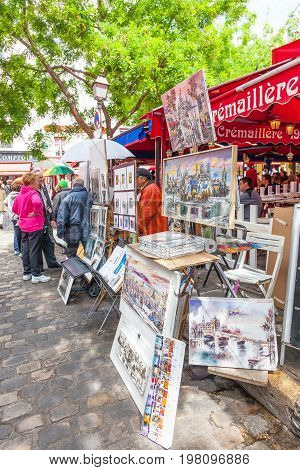 PARIS, FRANCE - JUNE 6, 2012: Tourists viewing art for sale at outdoor stalls in Montmartre in Paris.