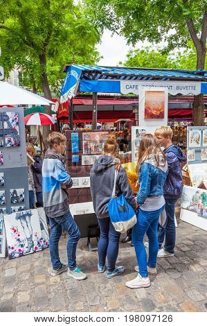 PARIS, FRANCE - JUNE 6, 2012: Young tourists viewing art for sale in Montmartre in Paris.