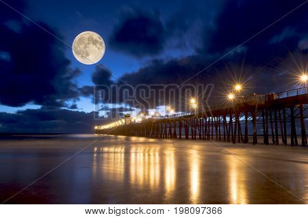 ocean pier at lighted at night with lights reflected in water and full moon in cloudy sky