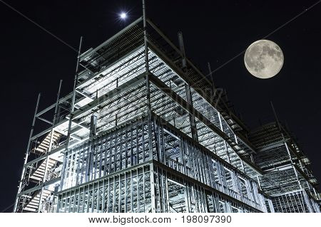 metal framing of high rise building under construction illuminated at night with full moon in sky