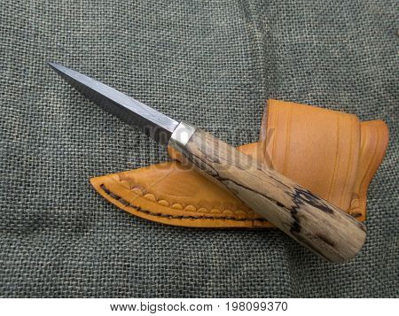A fixed blade damascus knife and leather sheath displayed on a blurred burlap background. Both items are hand crafted making them a unique set.