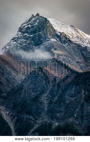 Fresh snow on a sunlit mountain peak in the Canadian Rockies, British Columbia, Canada after a snow storm.