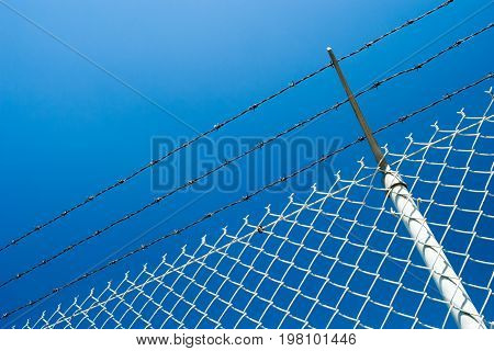 A chainlink fence with barbed wire against a clear blue sky.