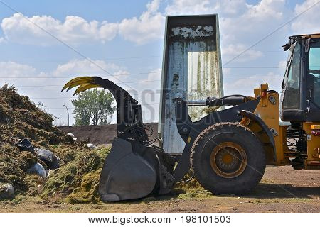 As a truck hydraulic  box loads a load of grass trimmings, a front end loader pushes it into a compost pile.