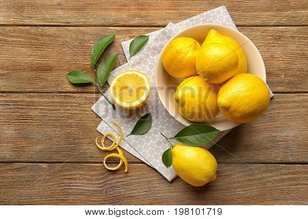 Bowl with delicious lemons on wooden table